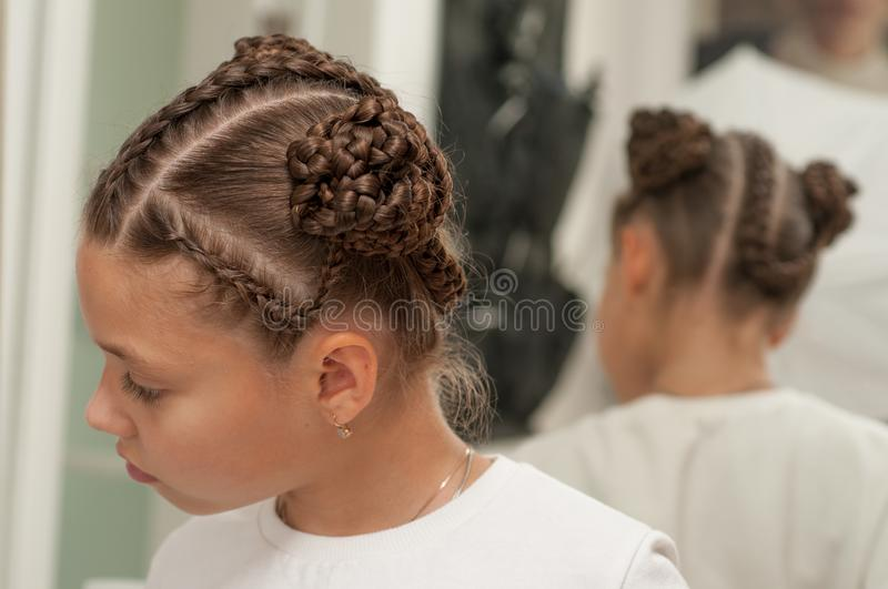 Braids on a girl. Beautiful hair weave on a girl with dark hair stock photo