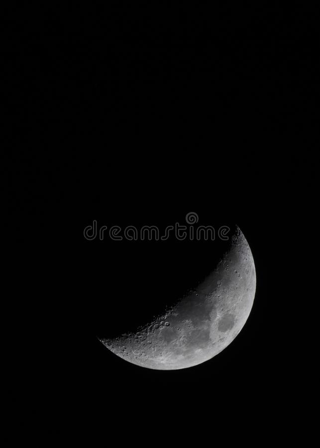 Half moon showing craters in night sky royalty free stock photo