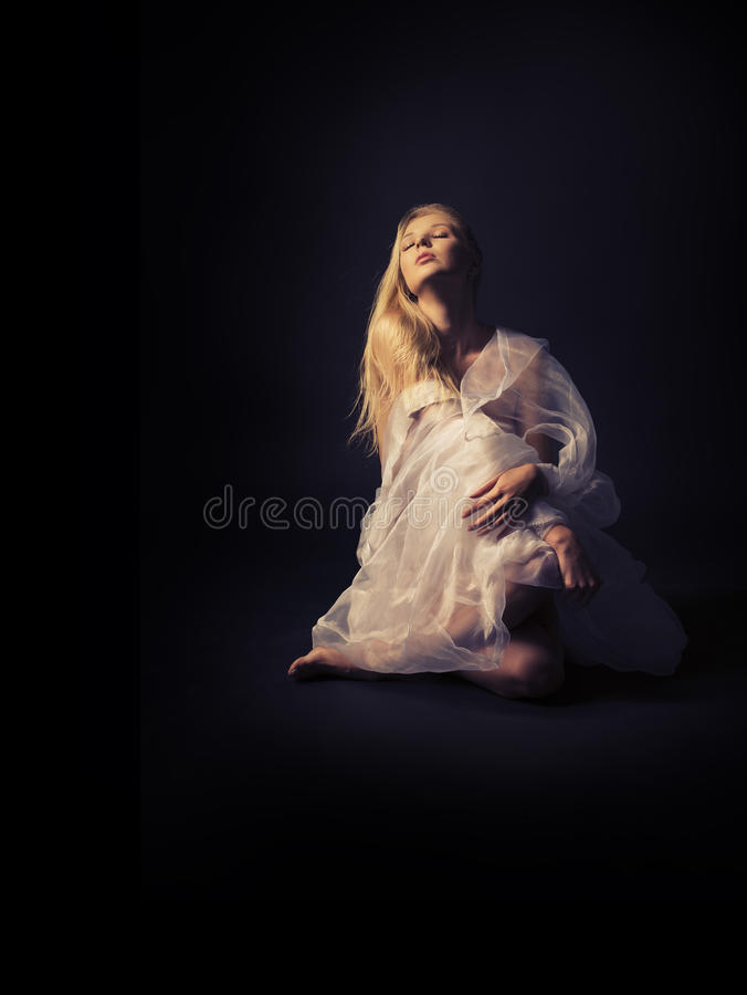 A beautiful half-naked girl in a white translucent clothes on a stock photos