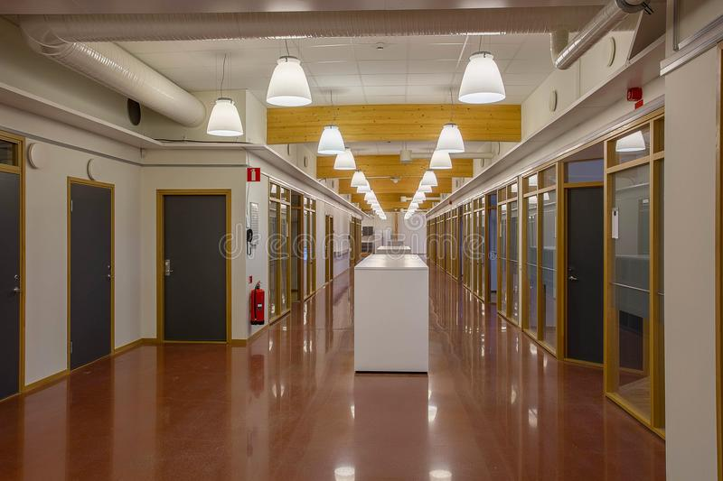 Beautiful hall in a modern building with multiply office rooms isolated. White walls and red-brown marble polished floor. Wooden a royalty free stock photos