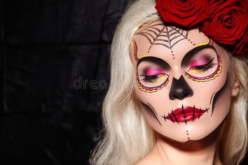 Beautiful Halloween Make-Up Style. Blond Model Wear Sugar Skull Makeup with Red Roses. Santa Muerte concept stock photo