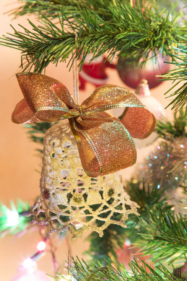 Beautiful hand made bell with bow on Christmas Tree royalty free stock photography