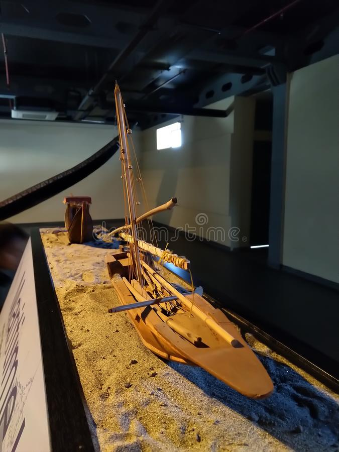 Beautiful Handmade model of boat laying on sand. Small crafted structure of boat. royalty free stock image