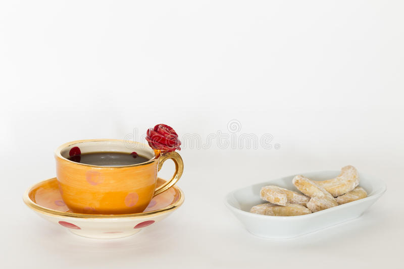 Beautiful handmade orange cup with red rose. A beautiful orange golden cup with red rose ornament and coffee and delicious cookies on a white plate royalty free stock photography