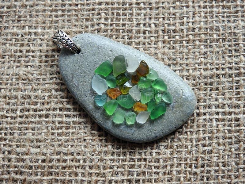 Handmade pendant using sea glass and sea stone , Lithuania royalty free stock photography