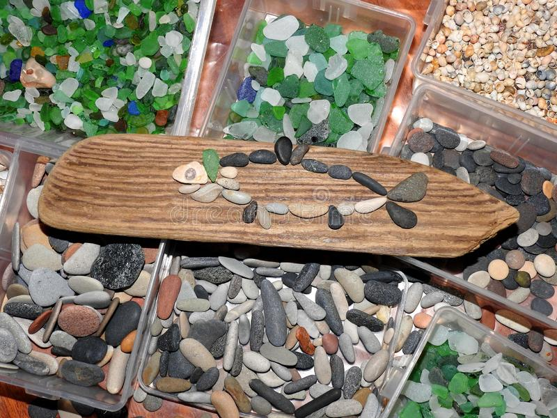Handmade picture - fish using sea wood, sea stones and sea glass royalty free stock photography
