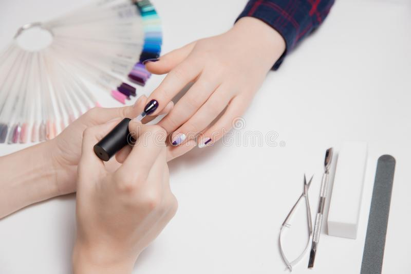 Beautiful hands woman manicurist hold brush for gel polish and apply coating on client nails in purple shirt. stock photo