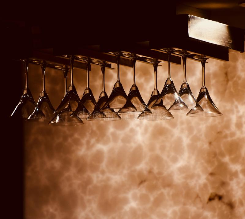 Beautiful hanging wine glasses of a bar isolated photograph. Beautiful transparent drinking glasses of a bar restaurant isolated unique transparent object stock images