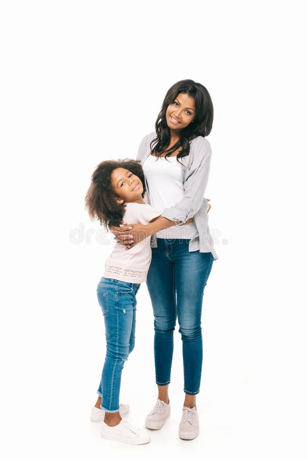 beautiful happy african american mother and daughter standing together and smiling at camera royalty free stock photo