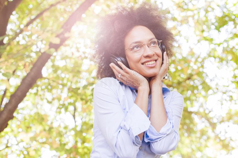 Beautiful Happy Afro American Young Woman Listening Music In Nature royalty free stock image