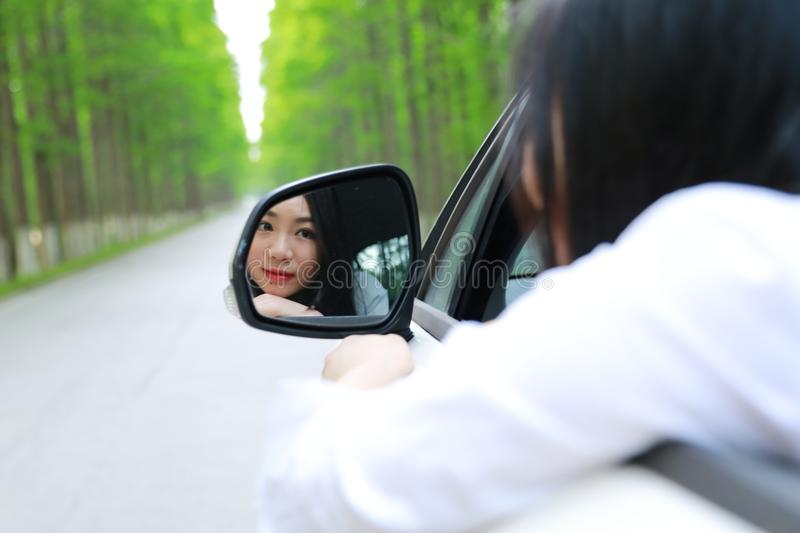 Beautiful happy Asian Chinese young woman sit on a white car look at herself from Automobile rearview mirror in summer safty drive royalty free stock photos
