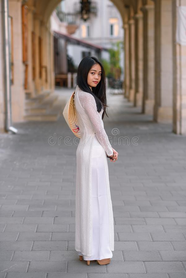 Beautiful happy asian girl dressed in Ao Dai dress with vietnamese conical hat against arches background. stock photography