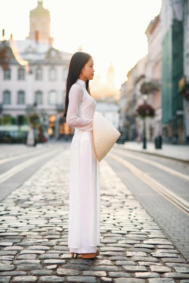Beautiful happy asian girl dressed in national traditional Ao Dai dress with vietnamese conical hat Non La, Leaf Hat. Asian girl walks on the street at sunrise royalty free stock photo