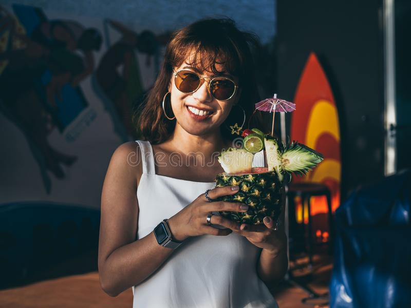 Beautiful happy asian woman wearing white sleeveless and sunglasses holding pineapple juice cocktail in summer stock photography