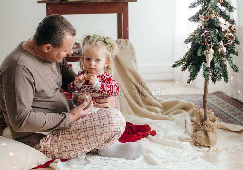 Beautiful happy baby girl with father near Christmas tree royalty free stock image