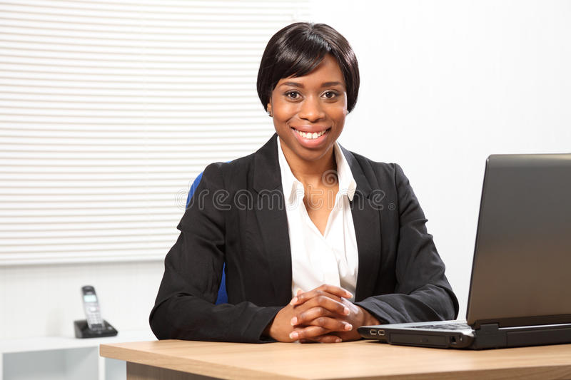 Beautiful happy black business woman in office. Happy young black woman working in office sitting to her desk with a beautiful smile royalty free stock images