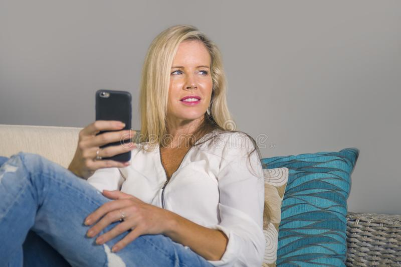 Beautiful happy blond woman early 40s relaxed at home living room using internet social media on mobile phone smiling sitting comf stock photography