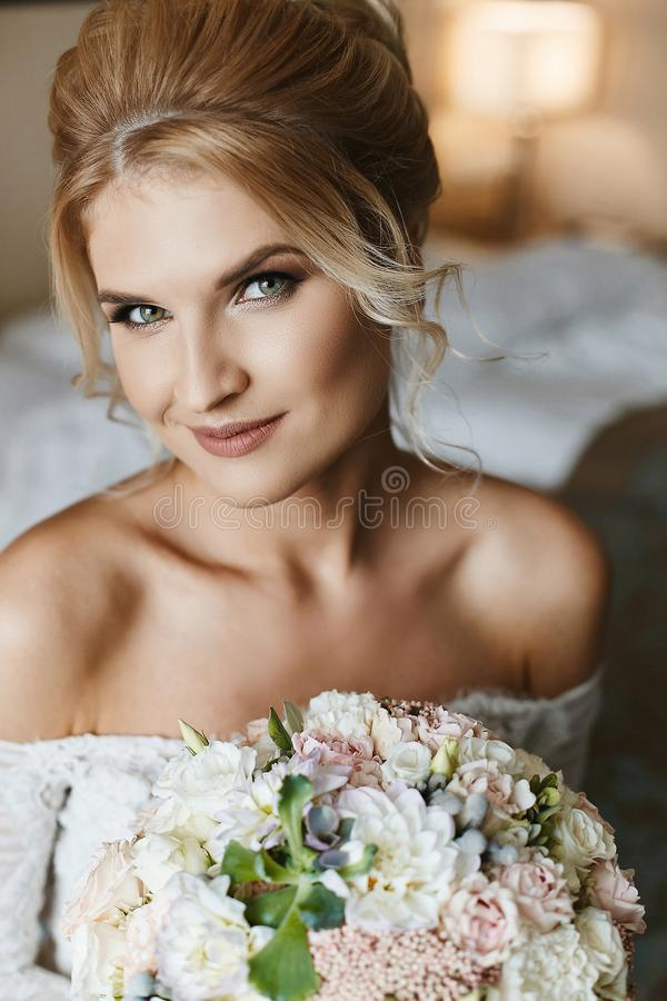 Beautiful and happy blonde model woman with green eyes in a wedding lace dress with a bouquet of flowers in her hand royalty free stock image