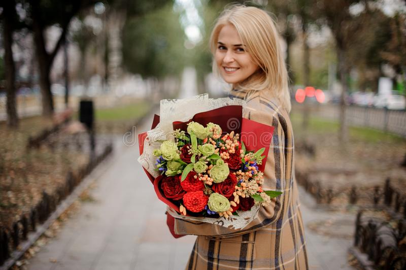 Beautiful happy blonde woman in plaid coat holding a bright bouquet of flowers walking on alley stock images