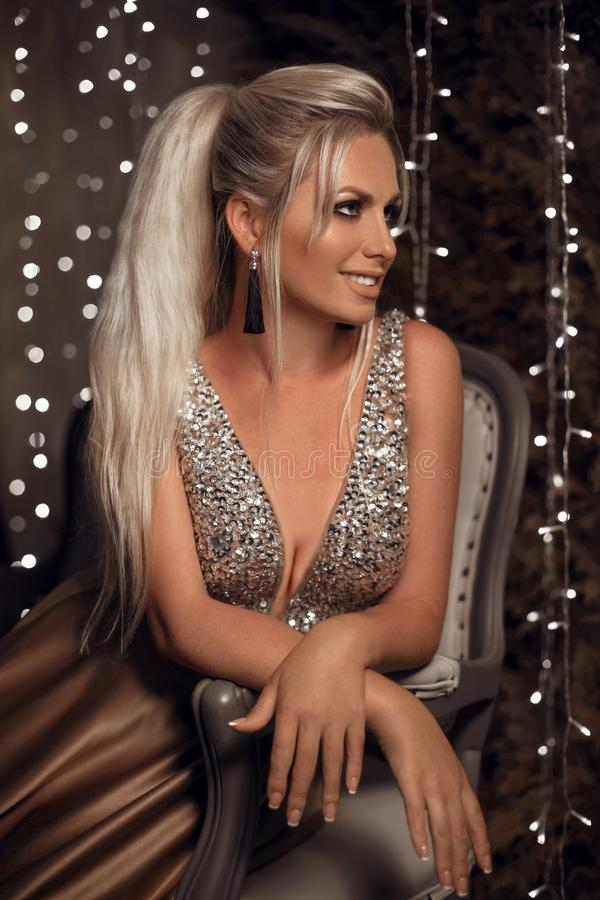 Beautiful happy blonde woman portrait with tassel earrings sitting on sofa over bokeh lights christmas dark background. stock images