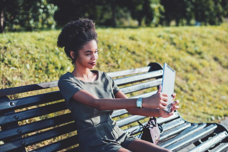 Young black cheerful female with tablet pc in park royalty free stock photography