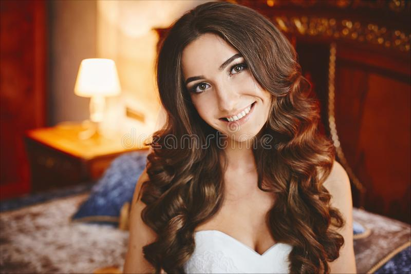 Beautiful and happy brunette model girl with stylish wedding hairstyle and with nude makeup in fashionable dress, a. Portrait of the young bride royalty free stock photo