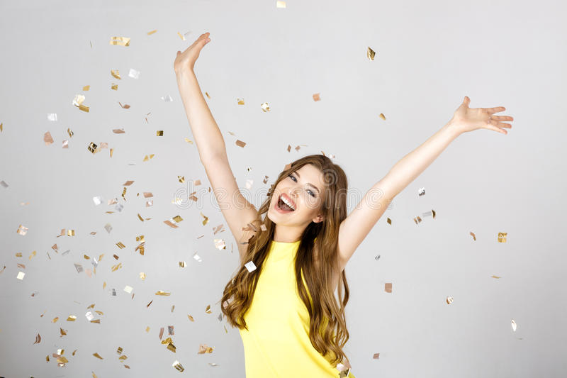 Beautiful happy brunette woman with long hair smiling and confetti falls everywhere. party time royalty free stock photos