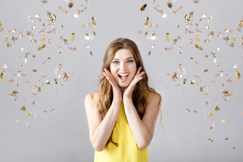 Beautiful happy brunette woman with long hair smiling and confetti falls everywhere. party time stock photos