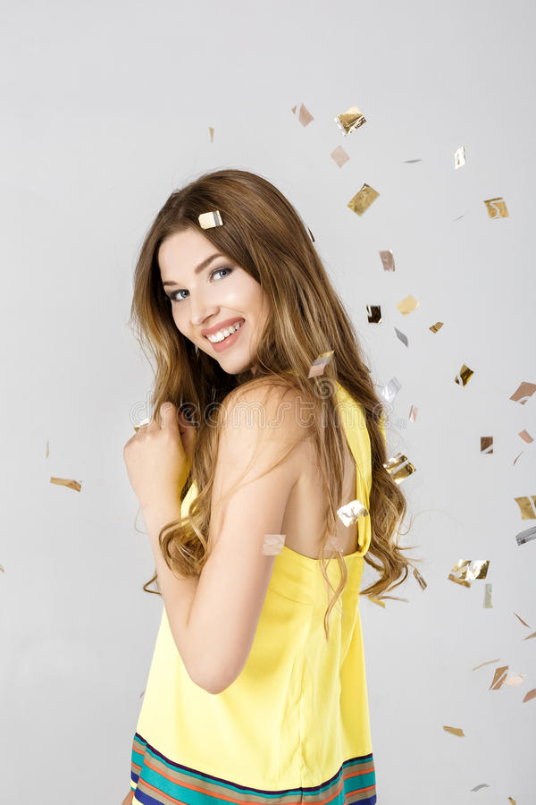 Beautiful happy brunette woman with long hair smiling and confetti falls everywhere. party time. Beautiful happy brunette woman with long hair smiling and royalty free stock photo