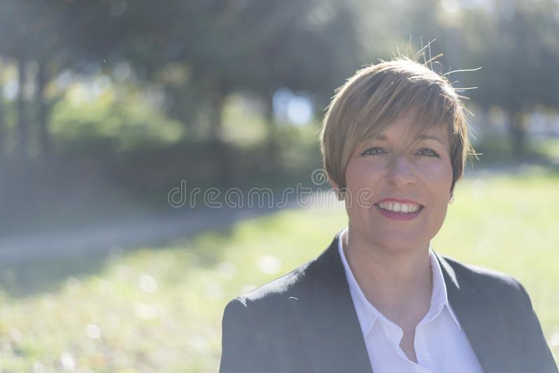 Beautiful happy business woman, sitting on bench stock photo