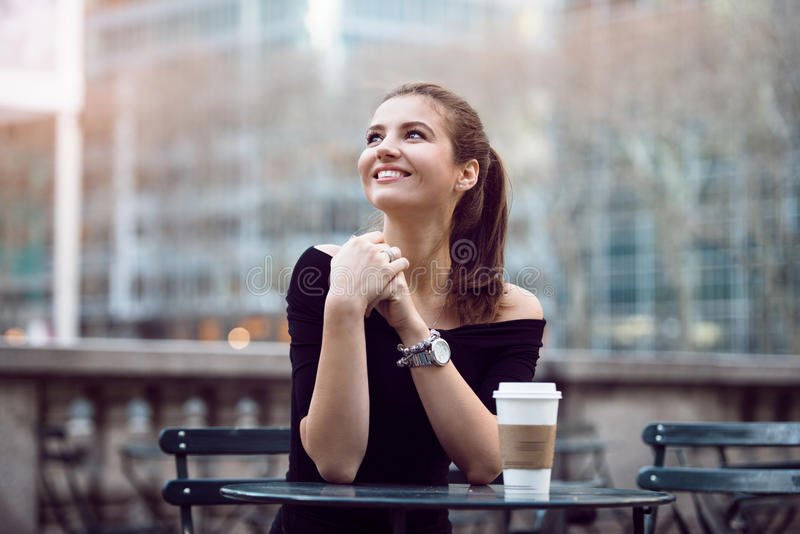 Beautiful happy businesswoman sitting in city park during lunch time or coffee break with paper coffee cup. stock images