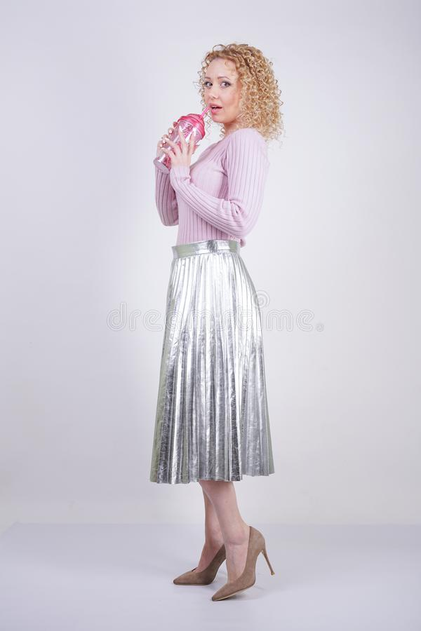 Beautiful happy caucasian woman with curly blonde hair stands in a thin pink knitted sweater and a metallic silver pleated long sk stock image