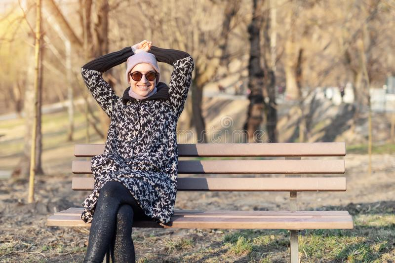 Beautiful happy caucasian  woman in jacket , hat and sunglasses enjoy  sitting on bench at city park or forest on sunny autumn day royalty free stock photography