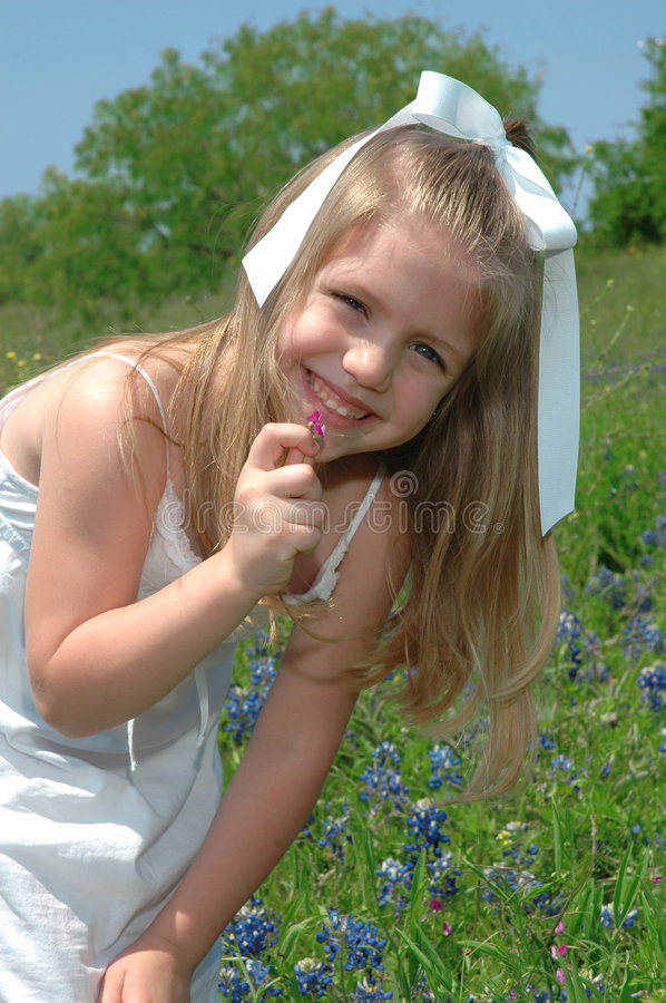 Beautiful Happy Child. Young girl searches threw the flowers for insects and lady bugs. Blue Bonnets are native Texas flowers. The Blue Bonnet is the State stock photos