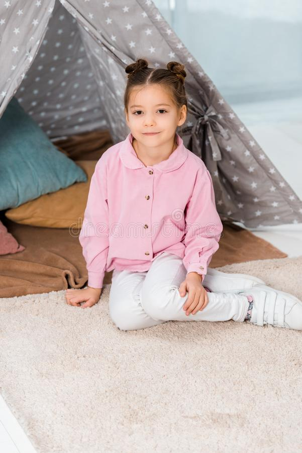 Beautiful happy child sitting on carpet near teepee and smiling. At camera stock images