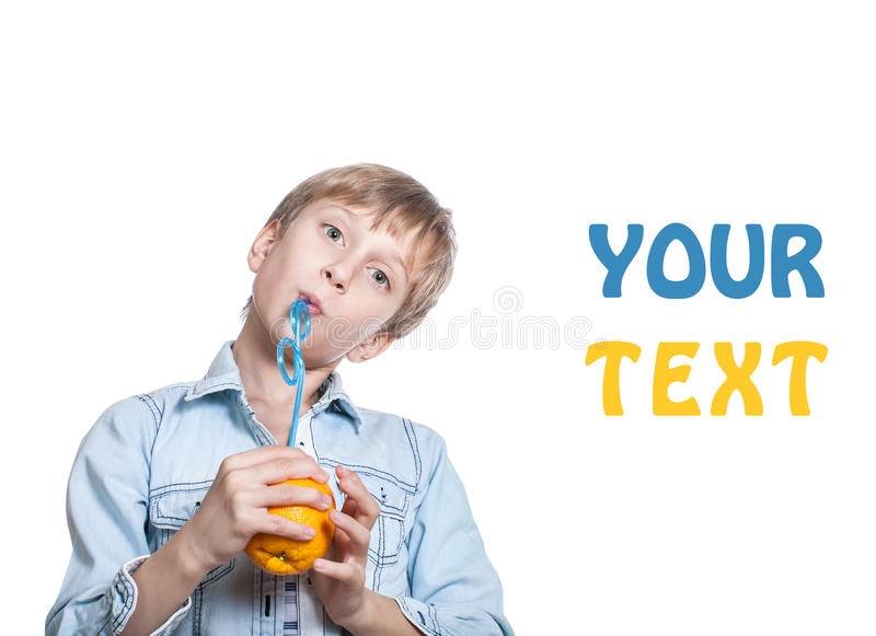 Beautiful happy child in stylish shirt drinks juice from an orange with a straw royalty free stock image