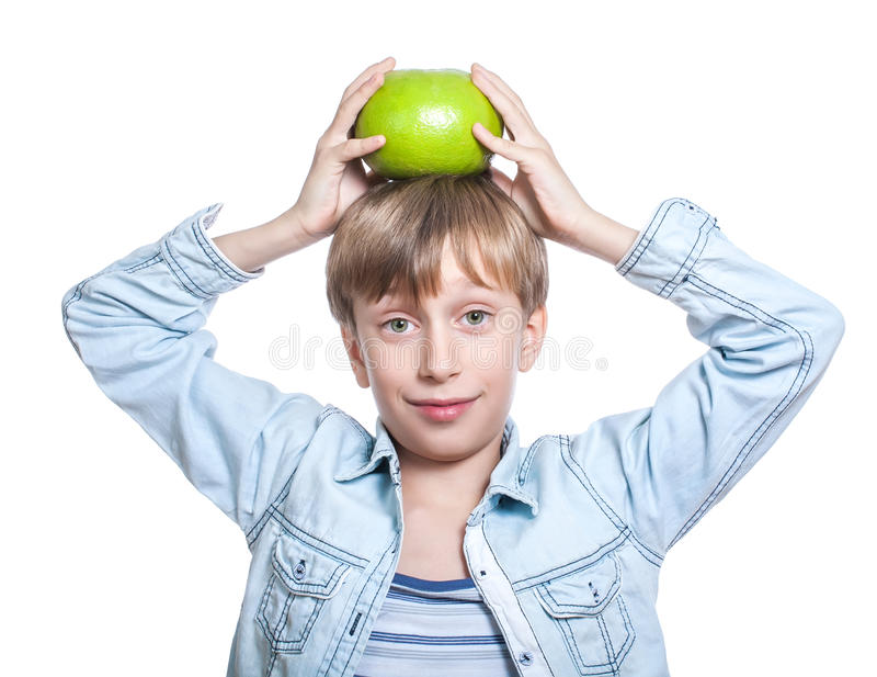 Beautiful happy child in stylish shirt shows a big grapefruit holding it on his head smiling stock image