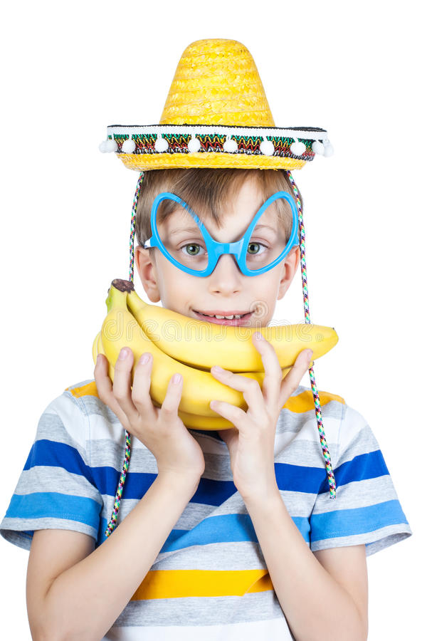 Beautiful happy child in stylish t-shirt wearing yellow sombrero holds a bunch of bananas smiling stock photo