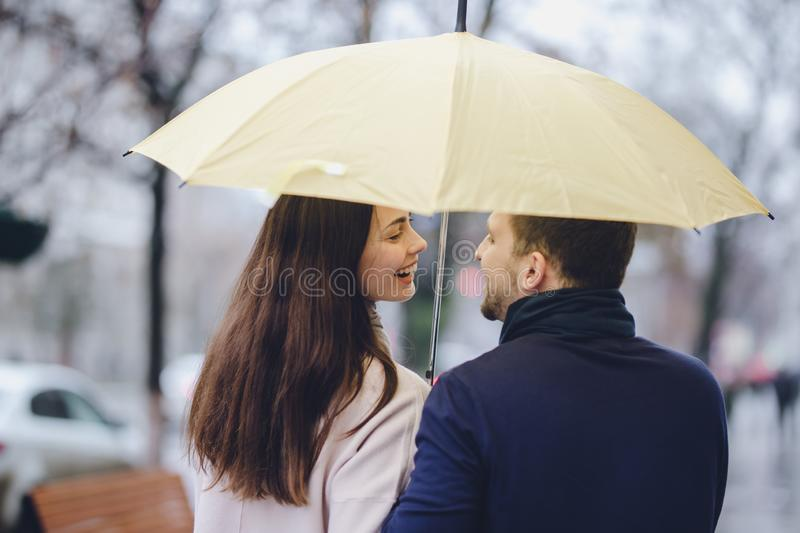 Beautiful happy couple, guy and his girlfriend dressed in casual clothes stand under the umbrella and look at each other royalty free stock photo