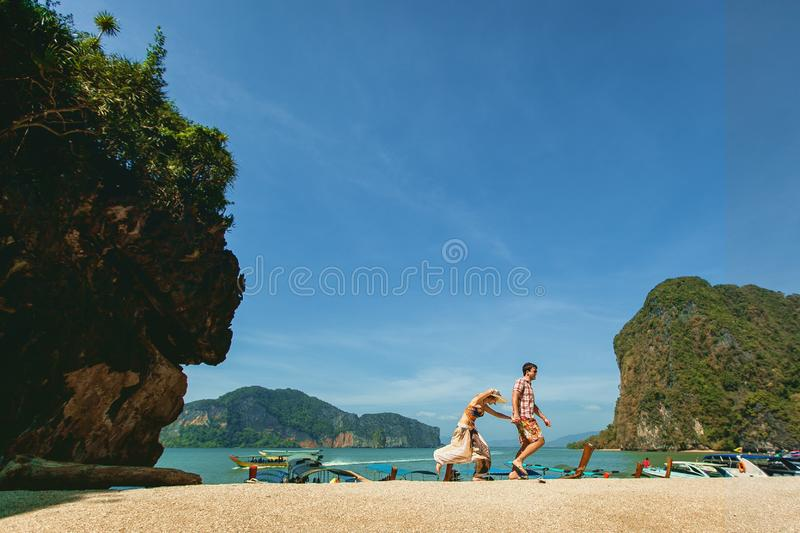 Beautiful happy couple, holding hands, walking on the beach against the sea and mountains. A girl in a hat and a guy on vacation stock images