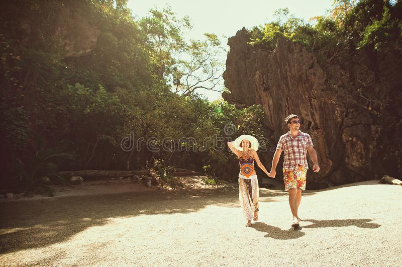 Beautiful happy couple holding hands, walking on the beach with mountains on a Sunny day, outdoors. A girl in a hat and a guy on royalty free stock images