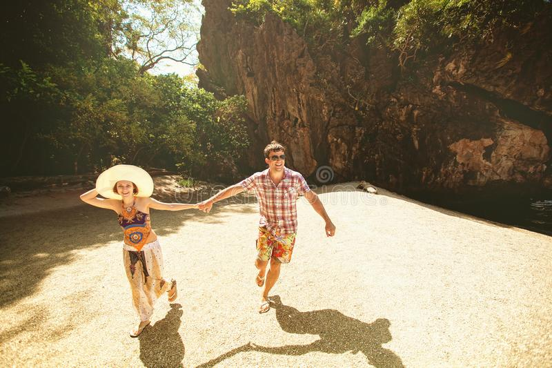 Beautiful happy couple holding hands, walking on the beach with mountains on a Sunny day, outdoors. A girl in a hat and a guy on stock photos