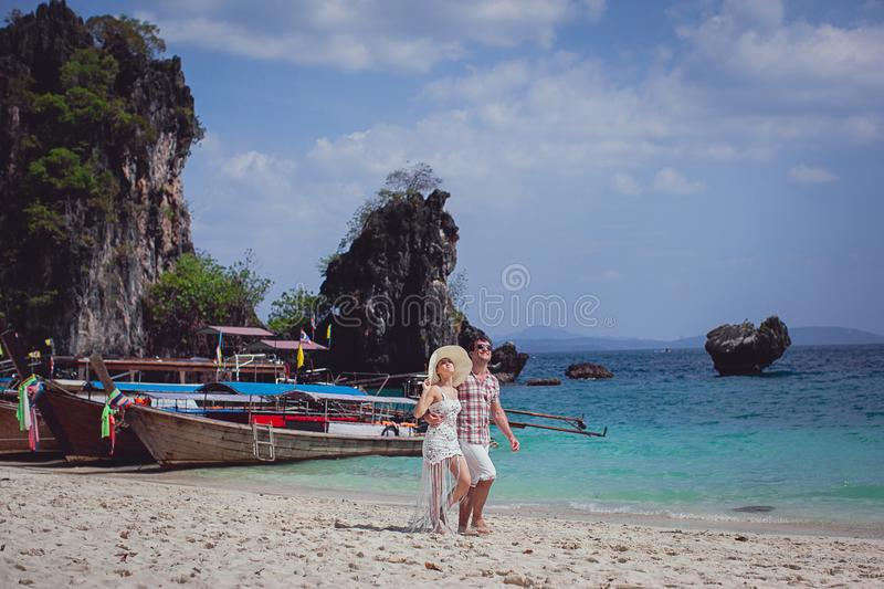 Beautiful happy couple, hugging, walking on the beach against the sea, mountains, gondolas. A girl in a hat and a guy on vacation stock photo