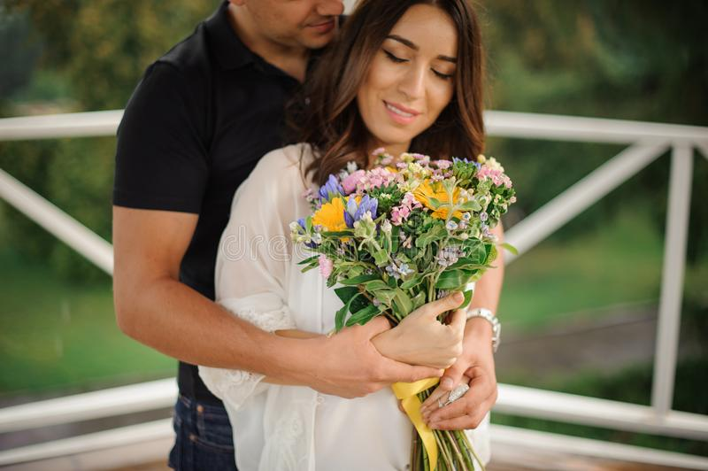 Beautiful and happy couple in love with bouquet of flowers stock images