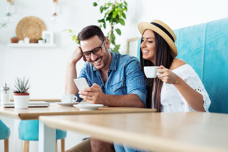 Happy couple man and woman sitting in modern cafe bar or restaurant and drinking coffee. stock image