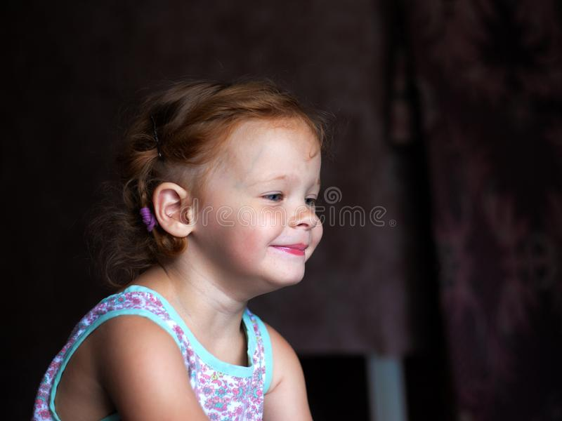 Beautiful happy cute little redhead girl smiles sincerely and laughs with a soft light from the window lifestyle stock image