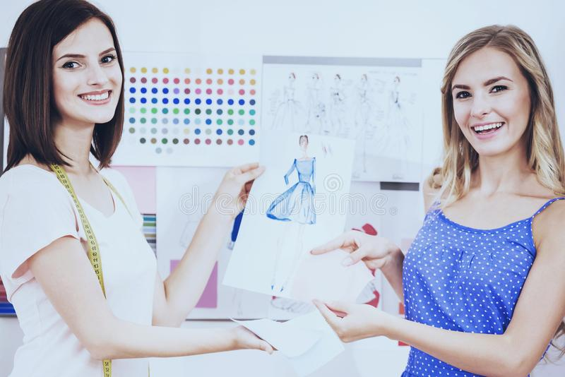 Beautiful and happy designers sitting in studio and demonstrating their sketch. stock photo