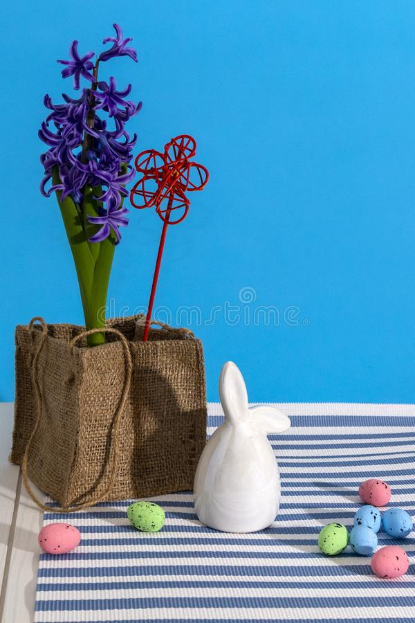 Beautiful happy easter for decorative design. Colorful eggs, bunny and flowers on blue background. Copy space royalty free stock photography