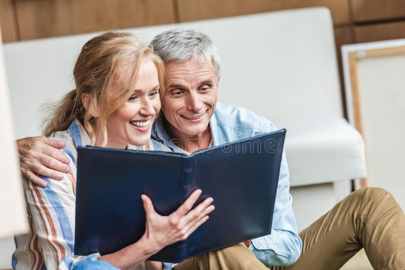 beautiful happy elderly couple looking at photo royalty free stock photos