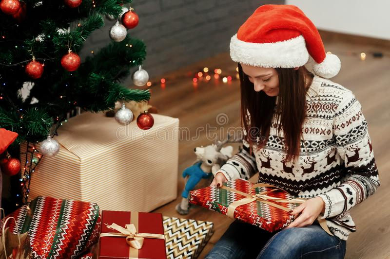 Beautiful happy emotional woman in red santa hat and reindeer sw. Eater smiling after receiving christmas presents near decorated christmas tree, greeting card royalty free stock image